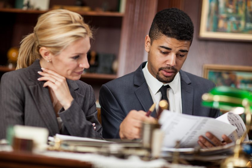 Female sitting with a male disability attorney looking over paperwork