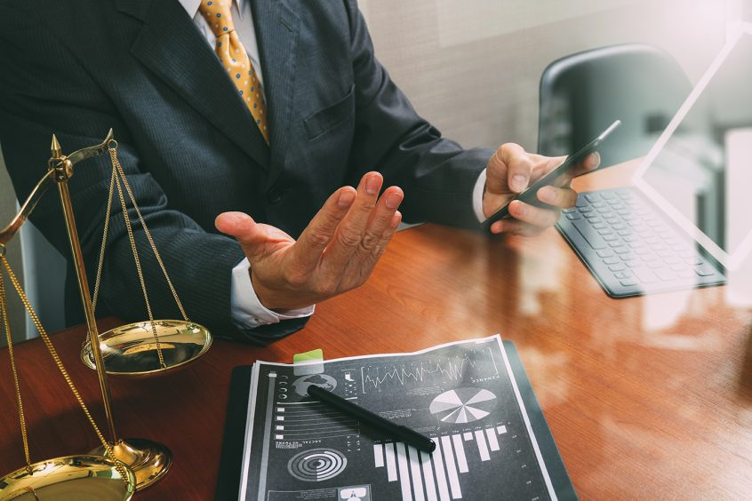 Male disability attorney sitting at a desk with a graph