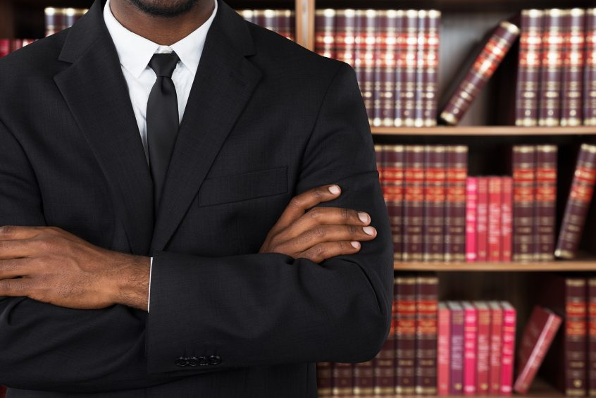 Male disability attorney standing in front of a bookcase