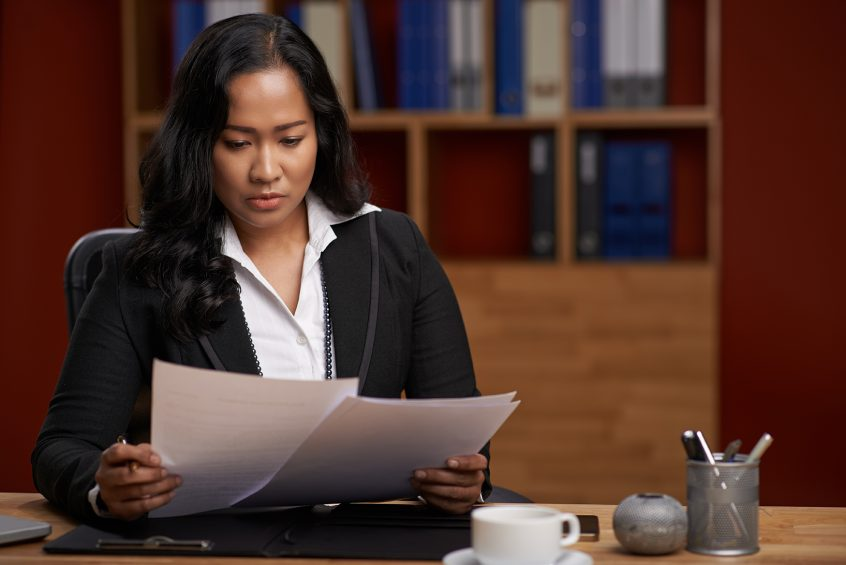 Female disability lawyer looking through paperwork at a desk